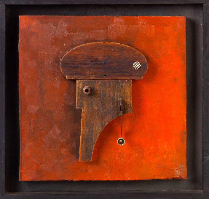 Escultura plana de madera sobre fondo pintado naranja que representa al perfil de un señor con boina