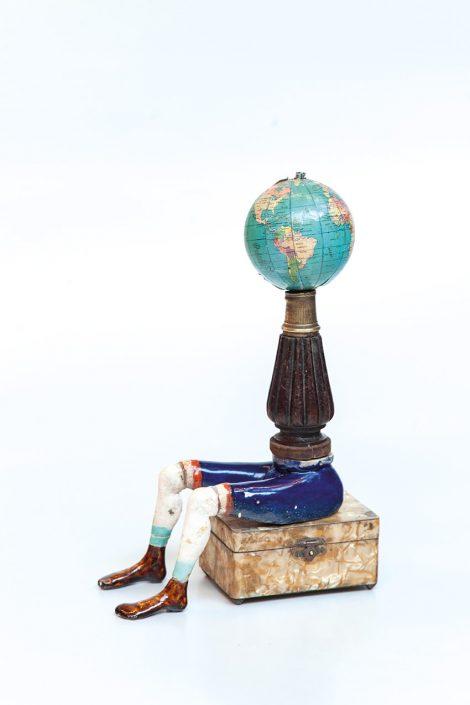 escultura de hombre con globo terráqueo como cabeza, hecha con elementos reutilizables