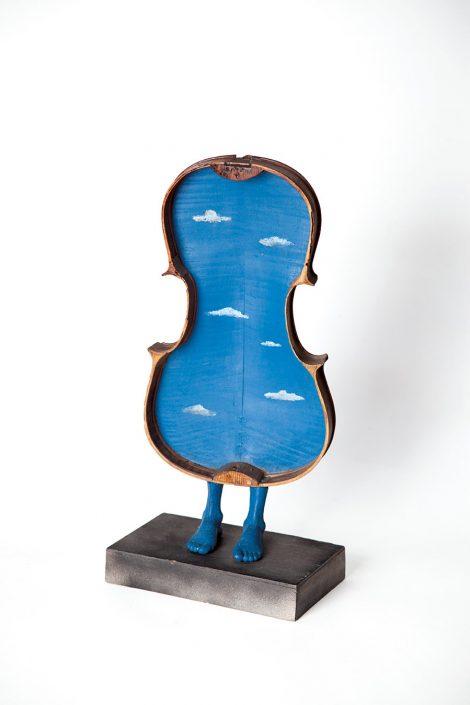 escultura hecha con caja de contrabajo y pies de estatua azules
